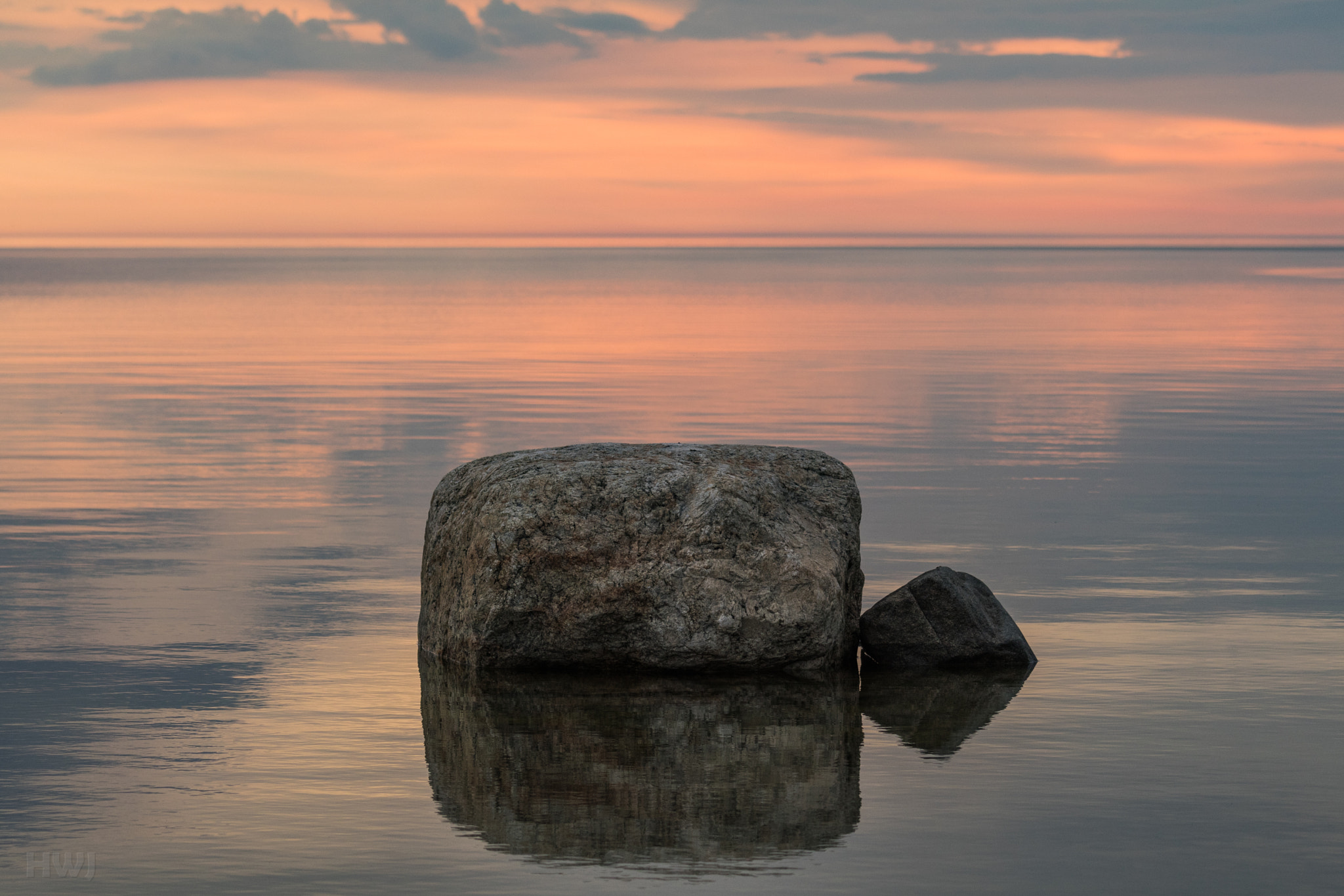 Photo of a rock in still water during a sunrise