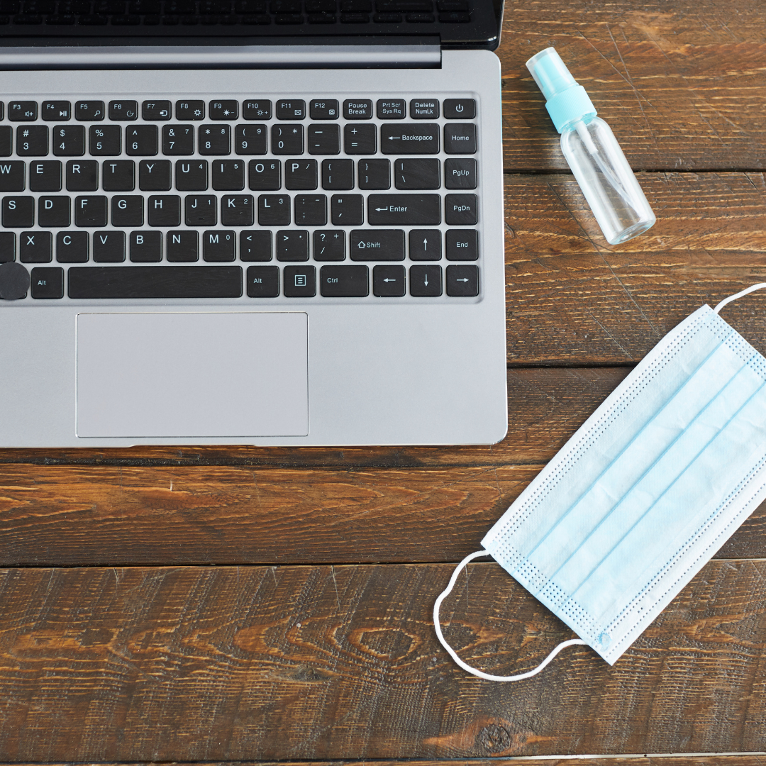 Photo a laptop on a desk next to a mask and a bottle of hand sanitizer.