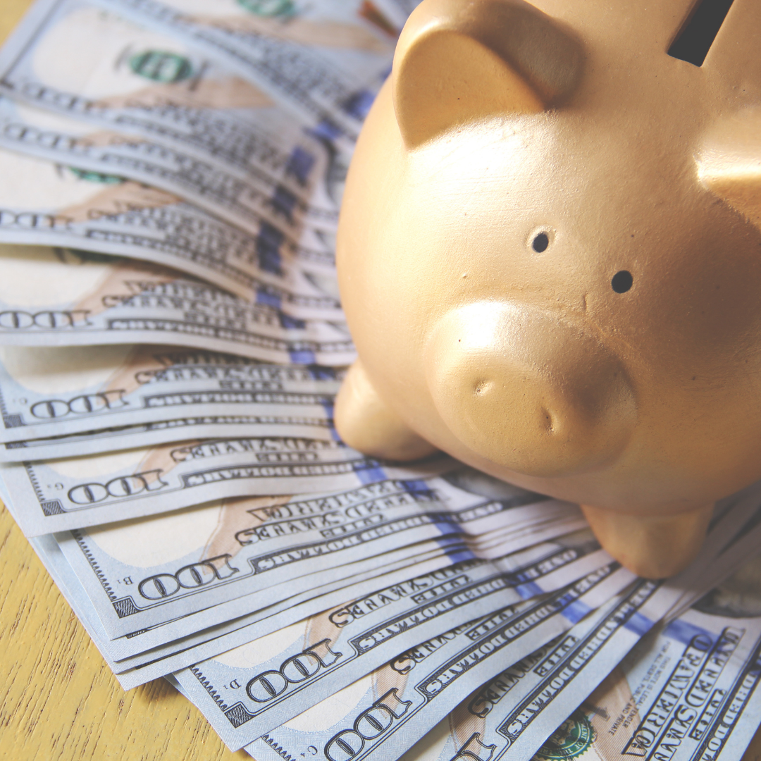 Photo of a golden piggy bank on a bed of cash money